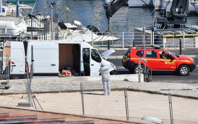 French forensic police officers search a vehicle following a car crash in the southern Mediterranean city of Marseille on August 21, 2017. (AFP/BERTRAND LANGLOIS)