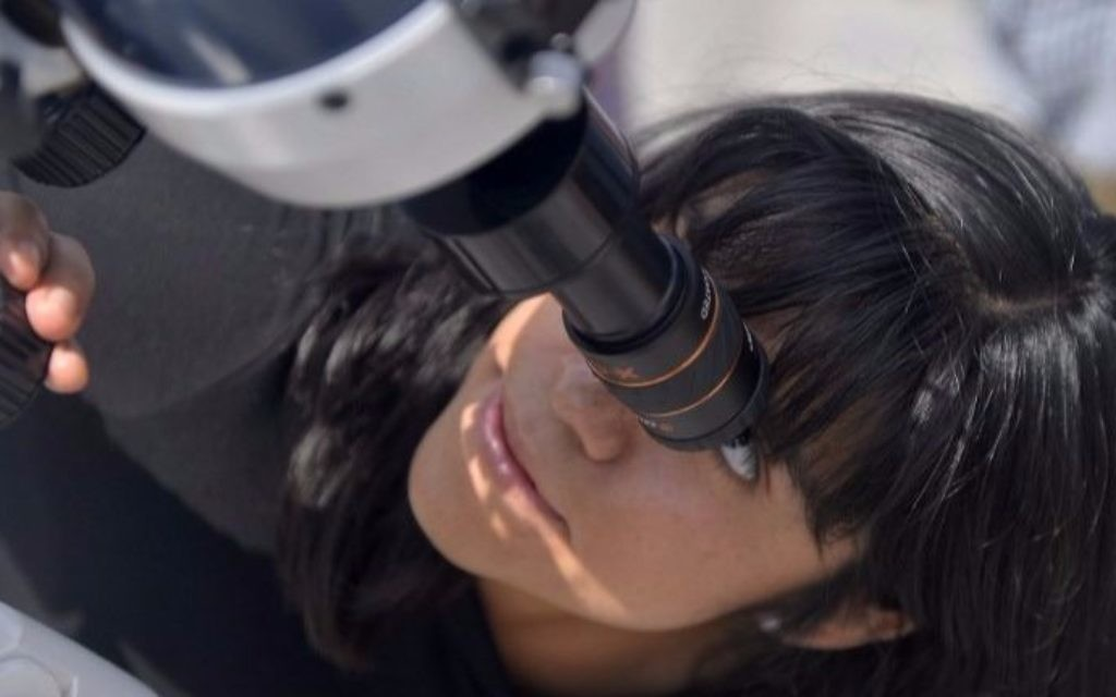 A Mexican girl looks through a telescope at the beginning of the solar eclipse, at the esplanade of the Museum of Natural History in Mexico City, on August 21, 2017. (Pedro Pardo/AFP)
