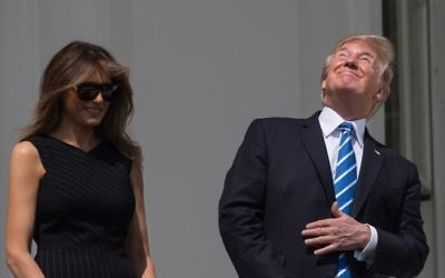 US President Donald Trump and First Lady Melania Trump look up at the partial solar eclipse from the balcony of the White House in Washington, DC, on August 21, 2017.(AFP PHOTO / NICHOLAS KAMM)