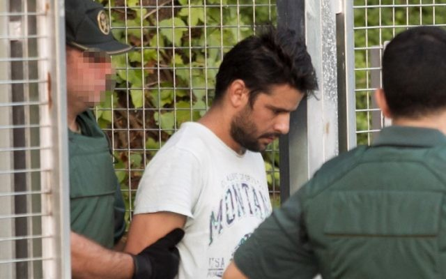 Mohamed Aallaa, suspected of involvement in the terror cell that carried out twin attacks in Spain, is escorded by Spanish Civil Guards from a detention center in Tres Cantos, near Madrid, on August 22, 2017 before being tranferred to the National Court.(AFP PHOTO / STRINGER)