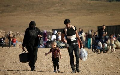 Syrians walk carrying their belongings on August 22, 2017 after crossing the Syria-Jordan border near the town of Nasib as they return to their homes following a US-Russia ceasefire brokered in three southern provinces, Daraa, Quneitra and Sweida earlier in the year. (AFP/Mohamad Abazeed)