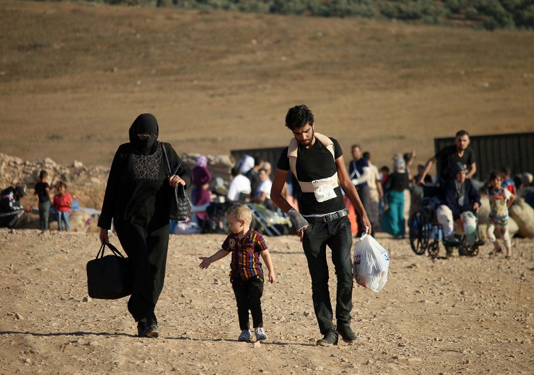 Syrians walk carrying their belongings on August 22, 2017 after crossing the Syria-Jordan border near the town of Nasib as they return to their homes following a US-Russia ceasefire brokered in three southern provinces, Daraa, Quneitra, and Sweida earlier in the year. (AFP/Mohamad ABAZEED)
