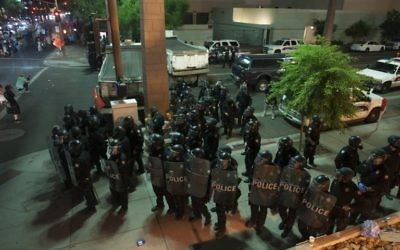 "Riot police form a line outside the Phoenix, Arizona, Convention Center where demonstrators gathered to protest US President Donald Trump's speech at a ""Make America Great Again"" rally on August 22, 2017. ( AFP PHOTO / Laura Segall)"
