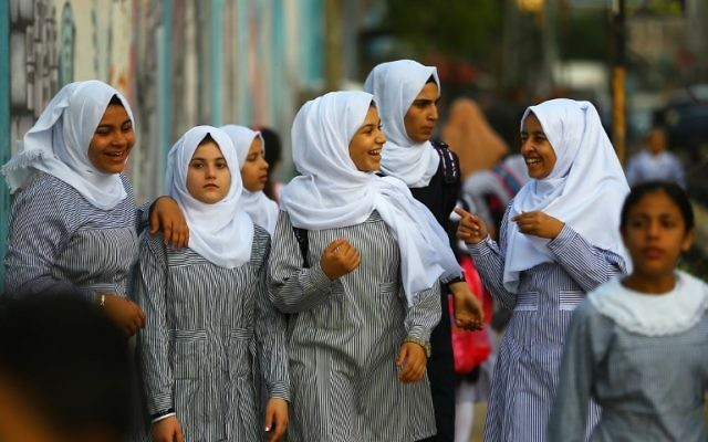 Illustrative: Palestinian schoolgirls chat as they head to school on the first day of a new academic year, at a United Nations-run school at the Al-Shatee refugee camp in Gaza City on August 23, 2017 (AFP/ MOHAMMED ABED)