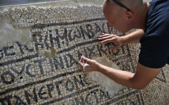 An archaeologist works on part of a 1,500-year-old mosaic floor bearing the names of Byzantine Emperor Justinian, at the Rockefeller Museum in Jerusalem, on August 23, 2017 (AFP PHOTO / AHMAD GHARABLI)