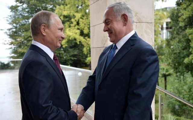 File: Russian President Vladimir Putin (L) greets Prime Minister Benjamin Netanyahu ahead of their meeting in Sochi on August 23, 2017. (AFP Photo/Sputnik/Alexey Nikolsky)