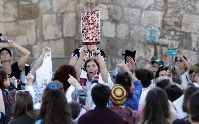 Members of Women of the Wall hold up a Torah scroll during a prayer service marking the first day of the Jewish month of Elul, on August 23, 2017, at the Western Wall in Jerusalem's Old City. (AFP Photo/Menahem Kahana)