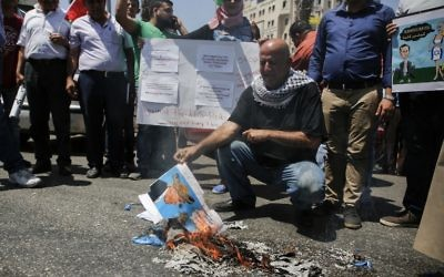 A picture taken on August 24, 2017 in the West Bank city of Ramallah shows a Palestinian holding a burnt flyer depicting US President Donald J. Trump defaced with cartoon shoes on his head, during a protest against the arrival of a US delegation headed by senior White House advisor Jared Kushner. (AFP/Abbas Momani)