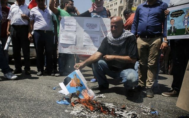 A picture taken on August 24, 2017 in the West Bank city of Ramallah shows a Palestinian holding a burnt flyer depicting US President Donald J. Trump defaced with cartoon shoes on his head, during a protest against the arrival of a US delegation headed by Senior White House Advisor Jared Kushner to meet with Palestinian president Mahmoud Abbas. (AFP PHOTO / ABBAS MOMANI)