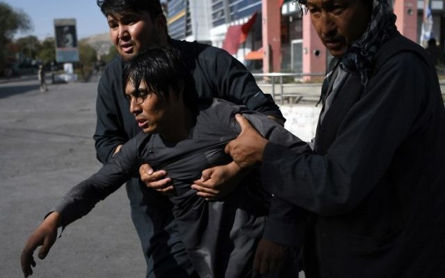 Afghan Shiite men carry a wounded friend near the site of suicide attack that targeted a Shiite mosque in Kabul on August 25, 2017. (AFP/Wakil Kohsar)