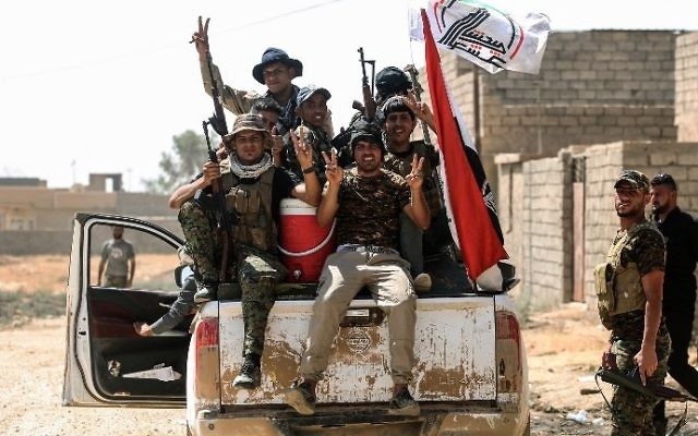 Fighters from the Shiite Popular Mobilization Forces flash the victory sign as they ride in a pickup truck during the advance in the the Islamic State held city of Tal Afar on August 25, 2017. (AFP Photo/Ahmad Al-Rubaye)