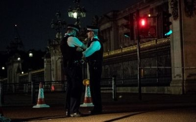 Police officers stand guard at a police cordon next to Buckingham Palace following an incident where a man armed with a knife was arrested outside the palace following a disturbance in London on August 26, 2017. (AFP PHOTO / CHRIS J RATCLIFFE)