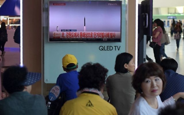People are seen past a television screen showing file news footage of a North Korean missile launch, at a railway station in Seoul on August 26, 2017. (AFP/Ed Jones)