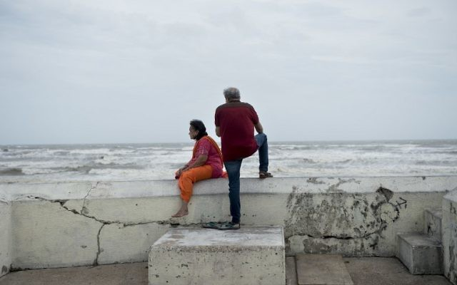 People look out from a seawall to the Gulf of Mexico as the effects of Hurricane Henry are seen August 26, 2017 in Galveston, Texas (AFP PHOTO / Brendan Smialowski)