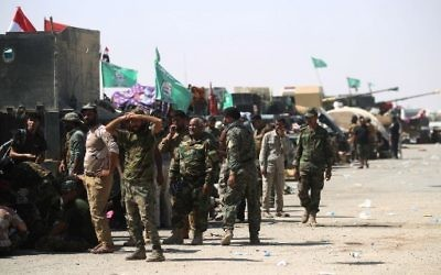 Fighters of Hashed Al-Shaabi (Popular Mobilization units) gather at the Tal Afar airport, west of Mosul, as Iraqi forces backed by local militia and a US-led coalition advanced in driving the Islamic State group from the city, on August 27, 2017. (AFP Photo/Ahmad al-Rubaye)