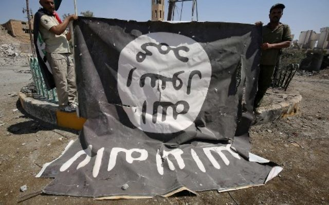 Fighters from the Hashed al-Shaabi (Popular Mobilisation units), backing the Iraqi forces, pose for a photograph with a flag of the Islamic State (IS) group in Tal Afar's Qalea central district during an operation to retake the city from the jihadists on August 27, 2017. (AFP Photo/Ahmad al-Rubaye)