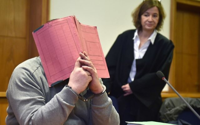 This photo taken on February 26, 2015 shows German former male nurse Niels H hiding his face behind a folder as he waits next to his lawyer Ulrike Baumann (R) for the opening of another session of his trial on February 26, 2015 at court in Oldenburg, northwestern Germany. (AFP PHOTO / DPA / CARMEN JASPERSEN)