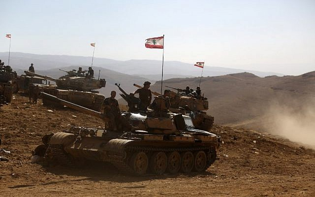 A picture taken on an army-organized press tour shows Lebanese army soldiers with the 6th Brigade standing on tanks flying the Lebanese flag in an area they recently took from the Islamic State (IS) group on the Syrian-Lebanese border, August 28, 2017. (AFP/PATRICK BAZ)