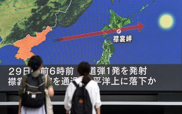 Pedestrians watch the news on a huge screen displaying a map of Japan (R) and the Korean Peninsula, in Tokyo on August 29, 2017, following a North Korean missile test that passed over Japan (AFP PHOTO / Toshifumi KITAMURA)