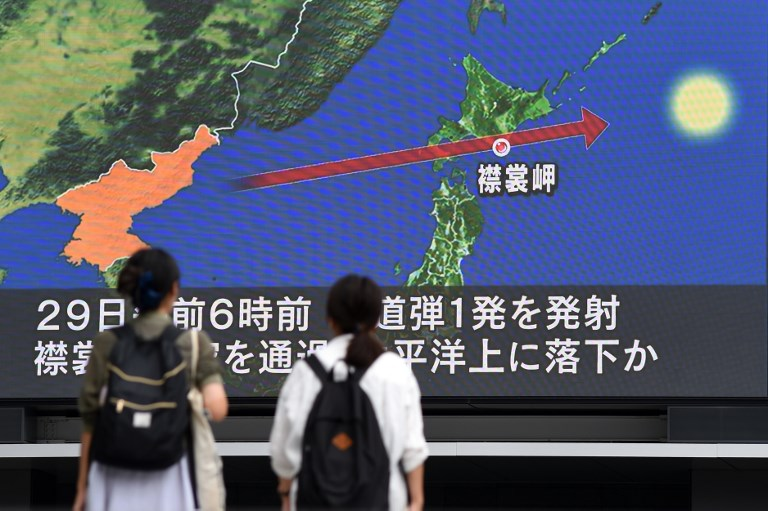 Pedestrians Watch The News On A Huge Screen Displaying A Map Of Japan R