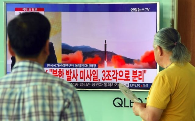 People watch a television news screen showing file footage of a North Korean missile launch, at a railway station in Seoul on August 29, 2017. AFP PHOTO / JUNG Yeon-Je)