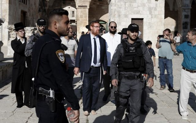 MK Yehuda Glick (C-L) walks barefoot, escorted by Israeli police and supporters, inside the flash-point Temple Mount complex in Jerusalem's Old City on August 29, 2017. (Ahmad Gharabli/AFP)