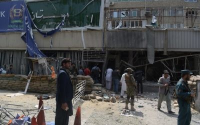 Afghan security personnel inspect the site of a suicide attack outside a bank near the US embassy in Kabul on August 29, 2017. (AFP PHOTO / SHAH MARAI)
