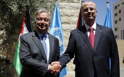 United Nations Secretary General Antonio Guterres (L) is greeted by Palestinian Authority Prime Minister Rami Hamdallah (R) in the West Bank city of Ramallah on August 29, 2017. (AFP Photo/Abbas Momani)