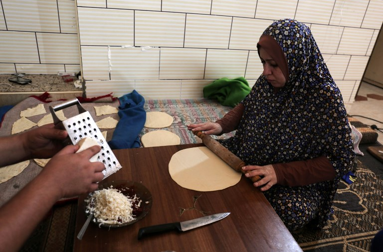 This photo taken on August 3, 2017 shows a Palestinian woman preparing bread during the few hours of mains electricity supply they receive every day, at Rafah refugee camp in the southern Gaza Strip. (AFP PHOTO / SAID KHATIB)