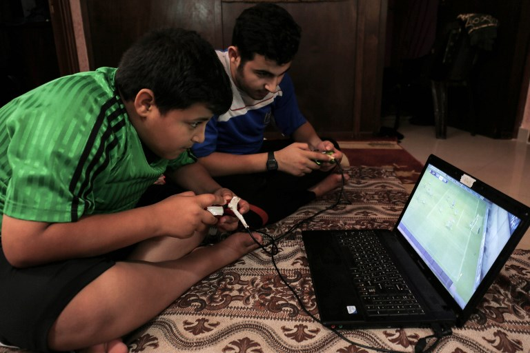 This photo taken on July 23, 2017 shows Palestinian boys playing on a laptop during the few hours of mains electricity supply their house receives every day, at Rafah refugee camp in the southern Gaza Strip. (AFP PHOTO / SAID KHATIB)