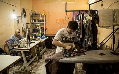 (FILES) This file photo taken on July 24, 2017 shows a Palestinian tailor using a sewing machine while an assistant irons a shirt during the few hours of mains electricity supply the residents of the Gaza Strip receive every day, in Gaza City. / AFP PHOTO / MAHMUD HAMS