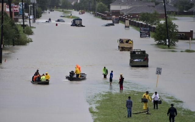 Volunteer rescuers evacuate people from a flooded residential area during the aftermath of Hurricane Harvey on August 29, 2017 in Houston, Texas. (AFP/Brendan Smialowski)