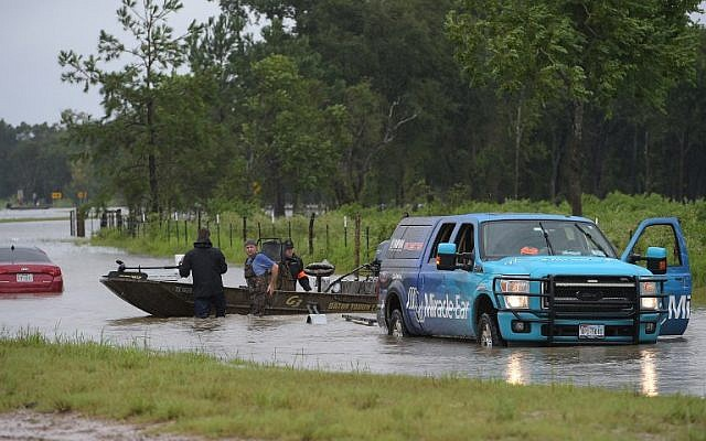 Civilian rescuers are seen before they set off on a flooded road to search for survivors in the aftermath of Hurricane Harvey in Cypress, Texas on August 29, 2017.President Donald Trump flew into storm-ravaged Texas Tuesday in a show of solidarity and leadership in the face of the deadly devastation wrought by Harvey -- as the battered US Gulf Coast braces for even more torrential rain. / AFP PHOTO / MANDEL NGAN