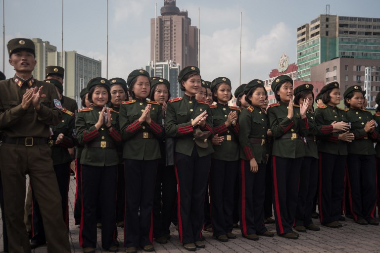 "Korean People's Army (KPA) soldiers applaud as they watch a screen showing news coverage of an August 29 missile test launch, in a public square outside a train station in Pyongyang on August 30, 2017. North Korea leader Kim Jong-Un has promised more missile flights over Japan, insisting his nuclear-armed nation's provocative launch was a mere ""curtain-raiser"", in the face of UN condemnation and US warnings of severe repercussions. / AFP PHOTO / KIM Won-Jin"