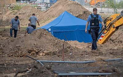 A policeman walks past a blue tent covering a British World War II bomb that was found during construction works on August 30, 2017 in Frankfurt am Main, western Germany. (AFP Photo/DPA/Boris Roessler/Germany OUT)