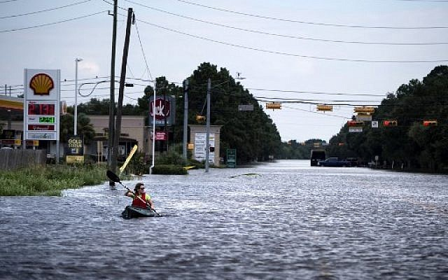 A woman paddles down a flooded road while shuttling deliveries for her neighbors during the aftermath of Hurricane Harvey on August 30, 2017 in Houston, Texas. (AFP Photo/Brendan Smialowski)