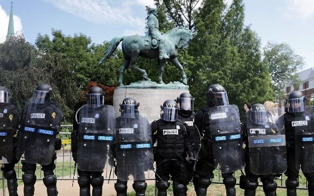 "Virginia State Police in riot gear stand in front of the statue of Confederate General Robert E. Lee before forcing white nationalists out of Emancipation Park after the ""Unite the Right"" rally was declared an unlawful gathering August 12, 2017 in Charlottesville, Virginia. (Chip Somodevilla/Getty Images/AFP)"