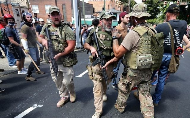 """White nationalist militamen evacuate protesters who were pepper sprayed after the """"Unite the Right"""" rally was declared a unlawful gathering by Virginia State Police August 12, 2017 in Charlottesville, Virginia. (Chip Somodevilla/Getty Images/AFP)"""