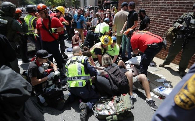 Rescue workers and medics tend to many people who were injured when a car plowed through a crowd of counter-demonstrators marching through the downtown shopping district August 12, 2017 in Charlottesville, Virginia. (Chip Somodevilla/Getty Images/AFP)