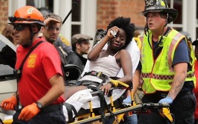 Rescue workers move victims on stretchers after car plowed through a crowd of counter-demonstrators marching through the downtown shopping district August 12, 2017 in Charlottesville, Virginia. (Chip Somodevilla/Getty Images/AFP)