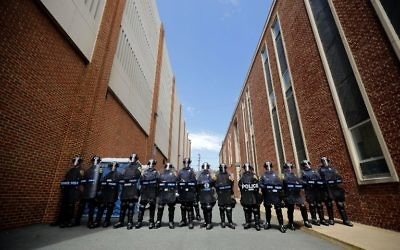Virginia State Police wear body armor and use riot shields while forming a cordon around police headquarters, where alt-right blogger Jason Kessler was taken after he tried to hold a news conference August 13, 2017 in Charlottesville, Virginia. Chip Somodevilla/Getty Images/AFP)