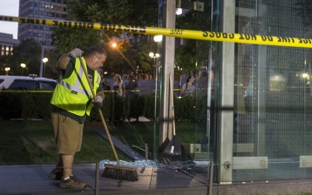 A worker cleans up broken glass at the New England Holocaust Memorial that was vandalized when a rock was thrown through a panel that was part of it on August 14, 2017 in Boston, Massachusetts. ( Scott Eisen/Getty Images/AFP)