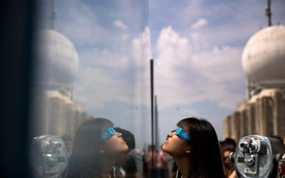 A woman views the solar eclipse at 'Top of the Rock' observatory at Rockefeller Center, August 21, 2017 in New York City. (Drew Angerer/Getty Images/AFP)