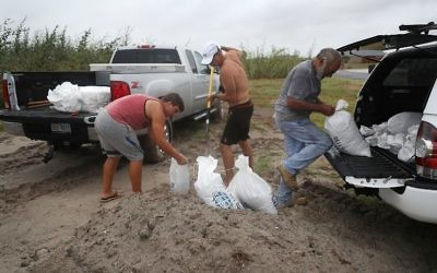 Cody Munds, Lee Martin and John Pezzi (L-R) fill sandbags as people prepare for approaching Hurricane Harvey on August 25, 2017 in Corpus Christi, Texas. (Joe Raedle/Getty Images/AFP)