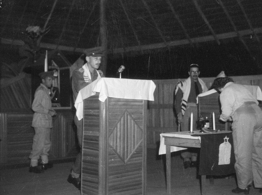Captain John Einfeld at the bima (dais) in the synagogue at headquarters, New Guinea Force, in August 1944, assisting Chaplain Goldman (right) with a Rosh Hashana service. (Courtesy)