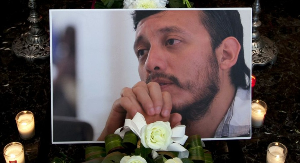 In this Aug. 3, 2015 file photo, a photograph of murdered photojournalist Ruben Espinosa sits among flowers and candles in front of his casket inside a funeral home before his wake begins in Mexico City.  (AP/Marco Ugarte, File)
