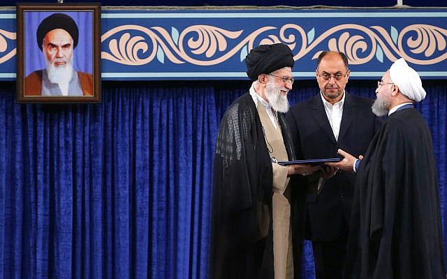 Supreme leader Ayatollah Ali Khamenei, left, gives his official seal of approval to President Hassan Rouhani as deputy chief of supreme leader's office Vahid Haghanian looks on in an endorsement ceremony in Tehran, Iran, Thursday, Aug. 3, 2017. A portrait of the late revolutionary founder Ayatollah Khomeini hangs at left. (Office of the Iranian Supreme Leader via AP)