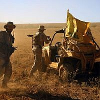 Hezbollah fighters stand on their army vehicle Al-Kheil Valley on the Lebanon-Syria border, July 29, 2017. (AP Photo/Bilal Hussein)