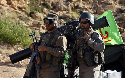 Hezbollah fighters stand on their army vehicle at the site where clashes erupted between Hezbollah and al-Qaeda-linked fighters in Wadi al-Kheil or al-Kheil Valley in the Lebanon-Syria border,  July 29, 2017. (AP Photo/Bilal Hussein)