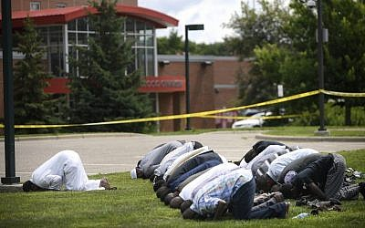 Mohamed Omar, left, the executive director of the Dar Al Farooq Center Islamic Center leads afternoon prayers outside the police tape surrounding the center Saturday Aug. 5, 2017 in Bloomington, Minn. (Aaron Lavinsky/Star Tribune via AP)